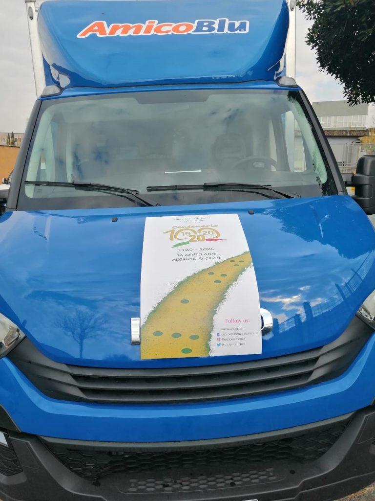 Foto frontale del camion con poster del centenario
