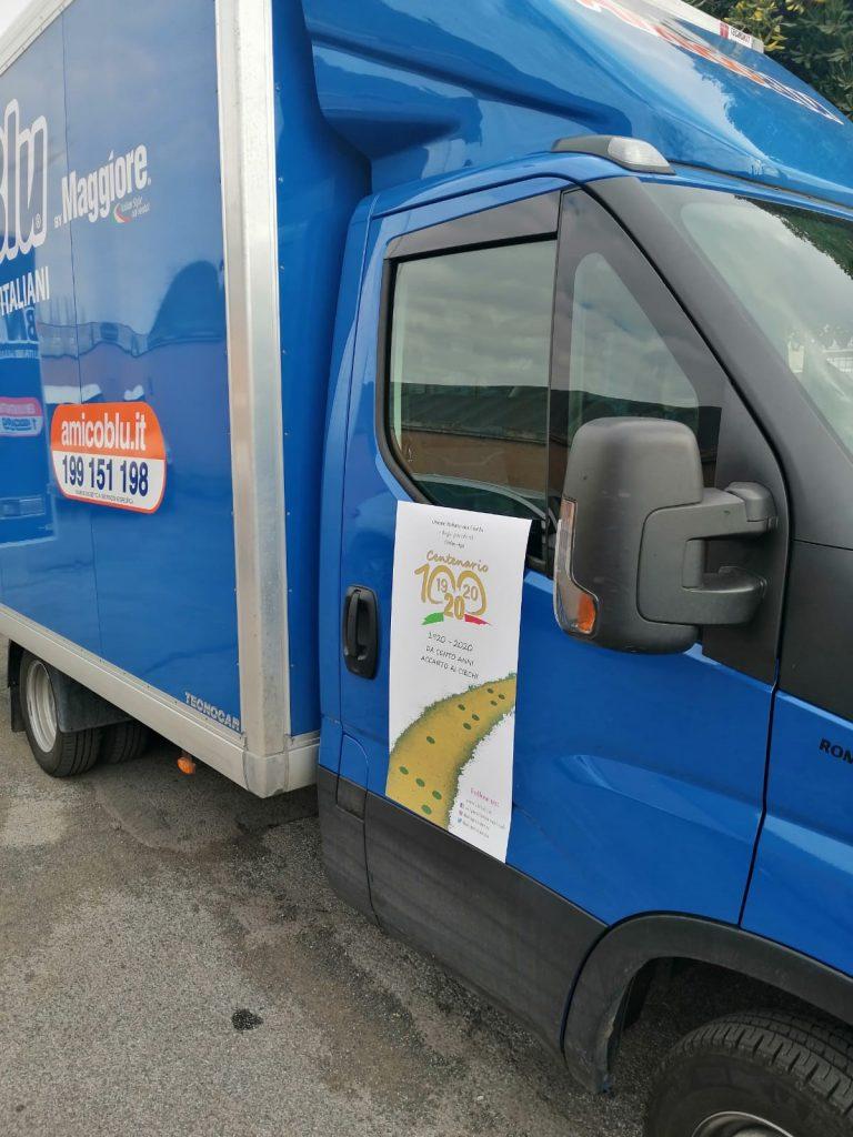 Foto laterale del camion con sopra il poster del centenario