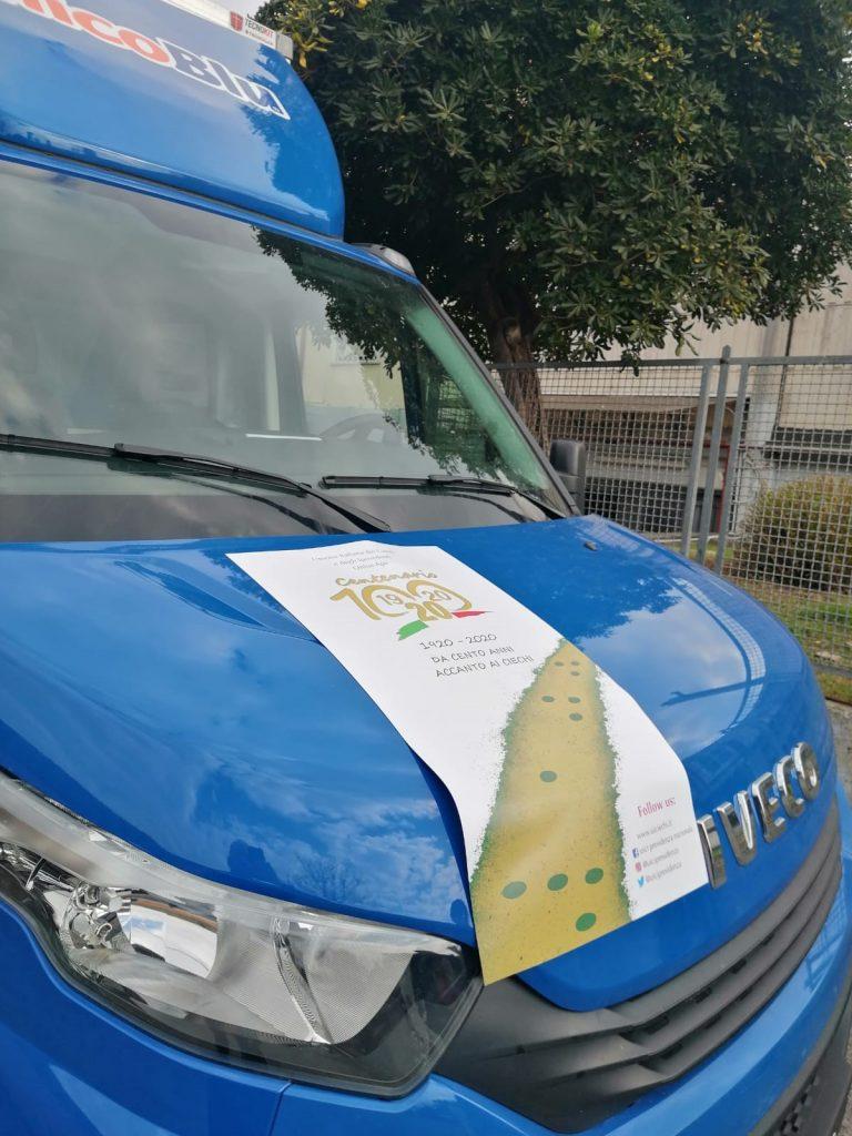 Foto frontale del camion con poster del centenario. Ripresa di lato.
